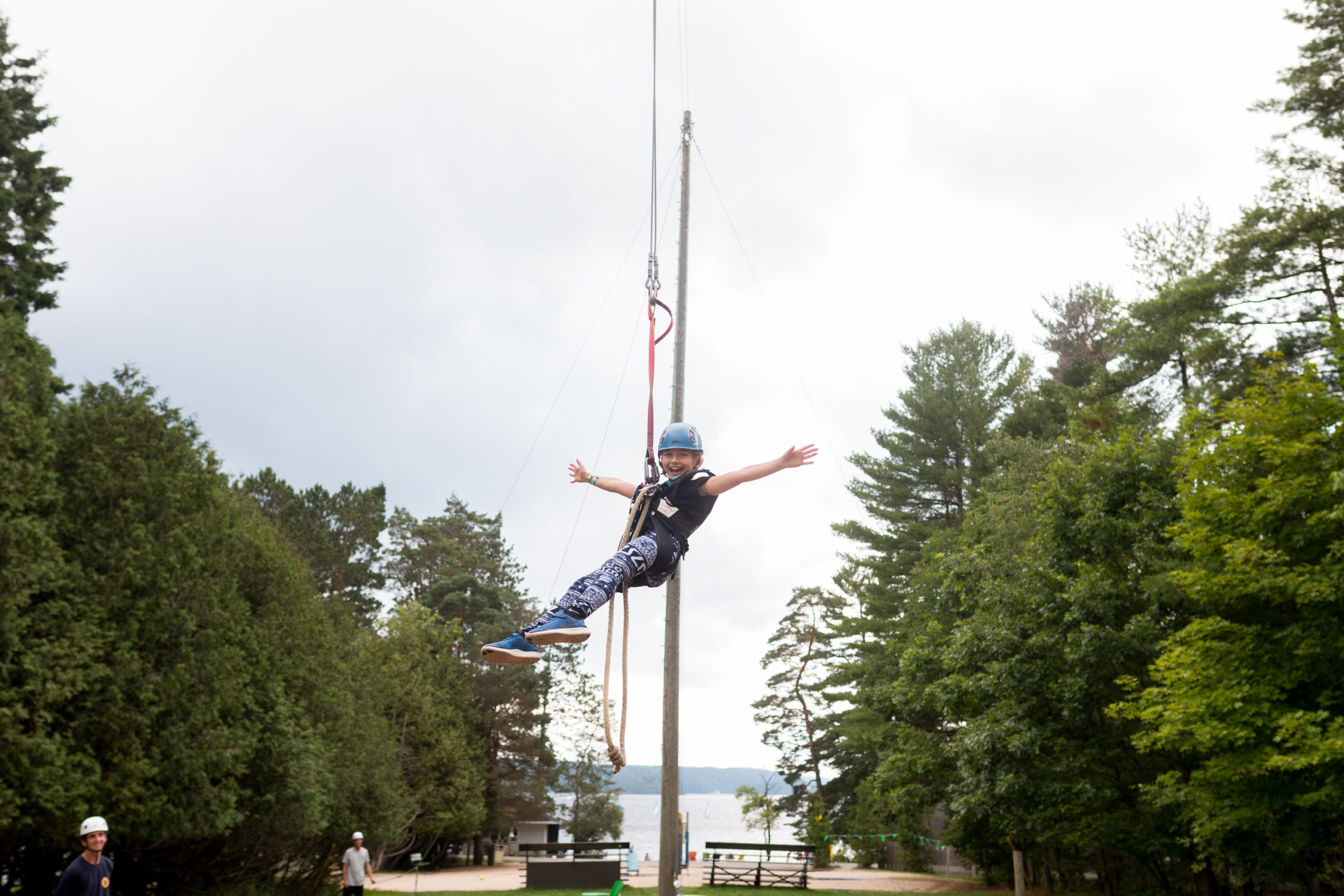 A girl enjoys a zipline ride with her arms reaching out to the sides
