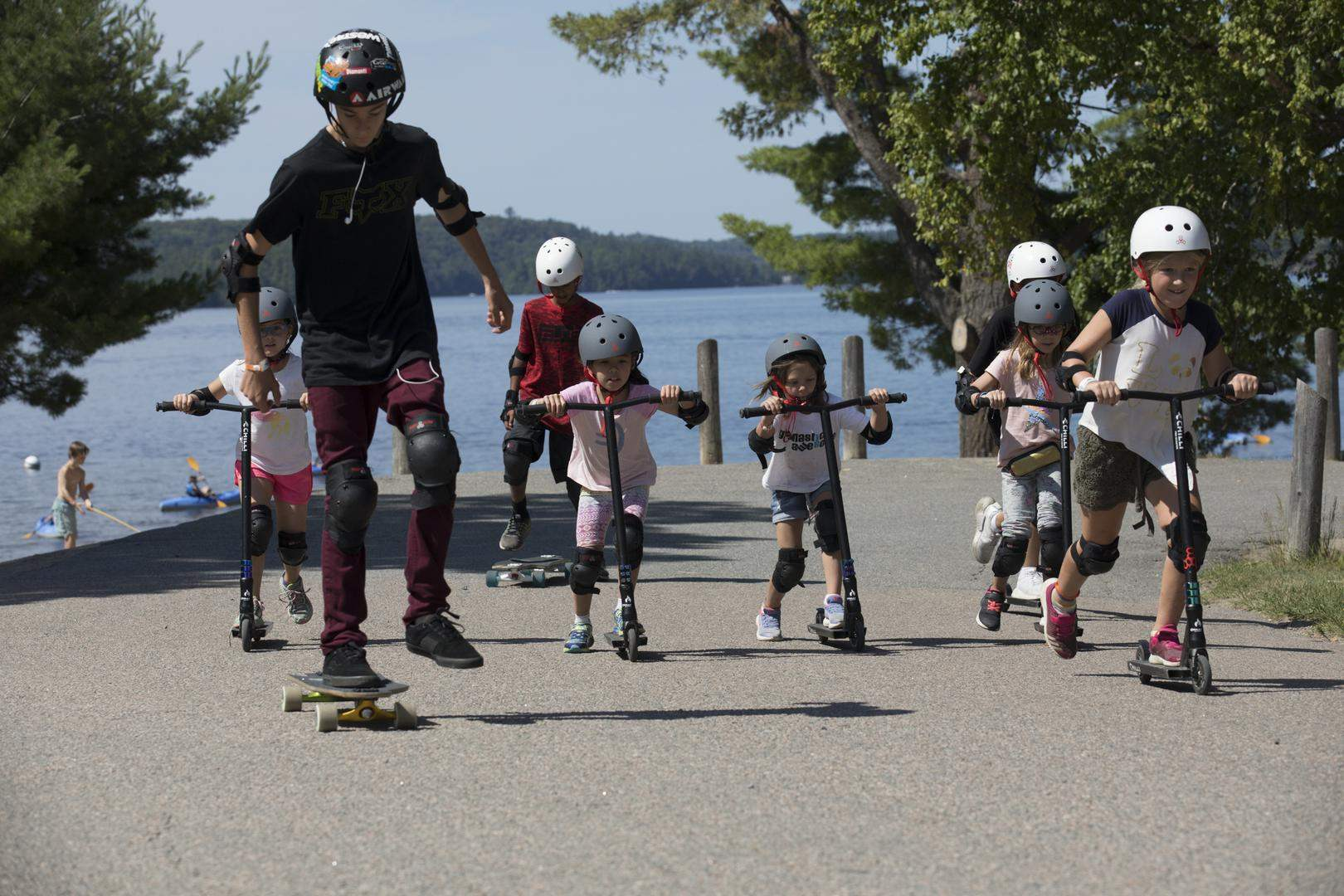 young boys and girls use scooters in front of a lake