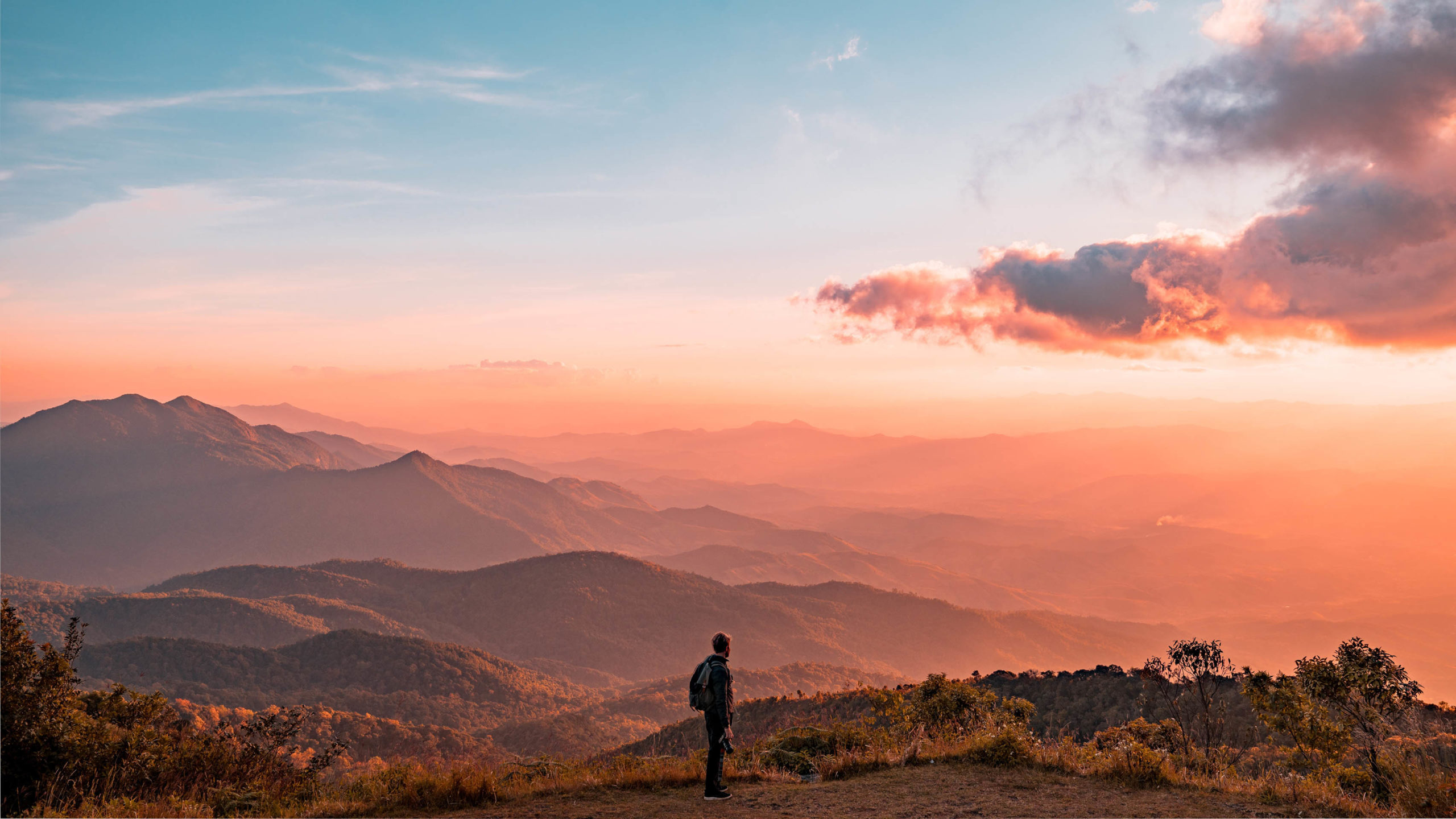 A silhouette of a man hiking on mountains