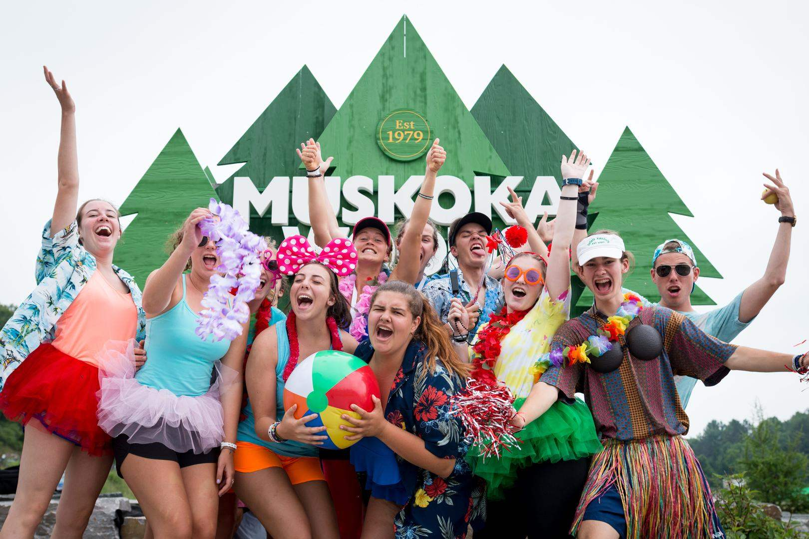Teenagers dressed in bright colours in front of the Muskoka Woods sign