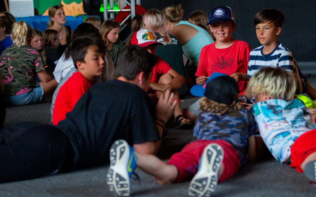 Muskoka Woods campers and staff lying on a floor chatting