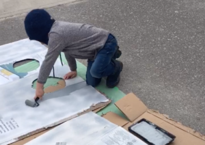 A young boy paints cardboard
