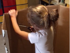 a young girl cuts a hole in cardboard